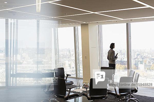 Nachdenklicher Geschäftsmann am sonnigen Bürofenster des Hochhauses
