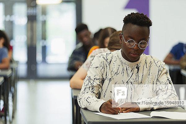 Fokussierter High-School-Schüler nimmt Prüfung am Schreibtisch im Klassenzimmer ab