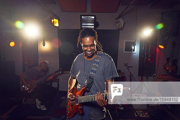 Männlicher Musiker spielt Gitarre im Aufnahmestudio