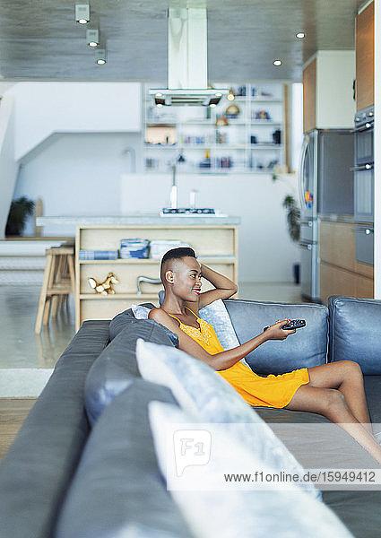 Junge Frau mit Fernbedienung  die auf dem Wohnzimmersofa fernsieht