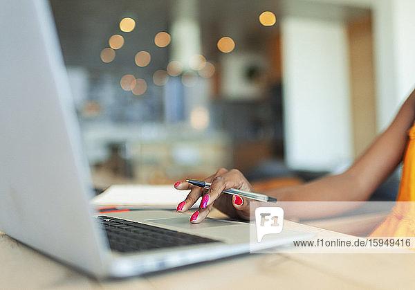 Junge Frau  die von zu Hause aus am Laptop arbeitet