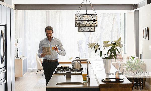Geschäftsmann liest Zeitung in der Morgenküche