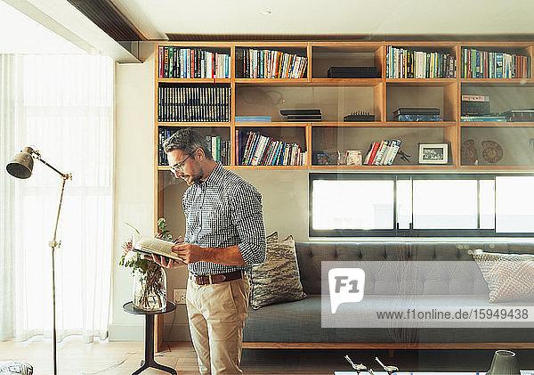 Mann liest Buch im modernen Wohnzimmer