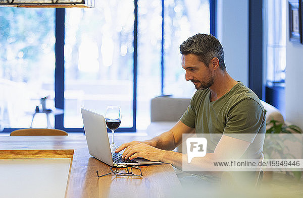 Mann benutzt Laptop und trinkt Wein  arbeitet von zu Hause in der Küche