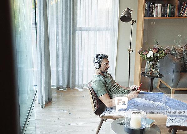 Mann entspannt sich im Wohnzimmer  hört Musik mit mp3-Player und Kopfhörern