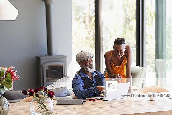 Vater und Tochter mit Laptop am Esstisch