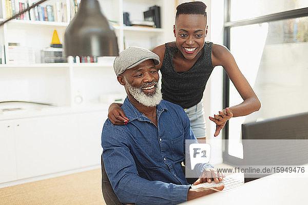 Glückliche Vater und Tochter unterhalten sich am Computer im Heimbüro