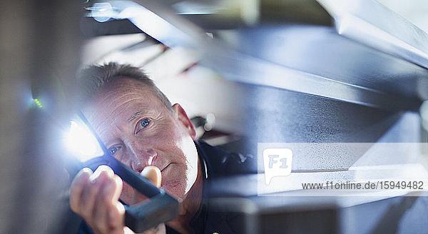 Männlicher Mechaniker mit Taschenlampe arbeitet unter dem Auto