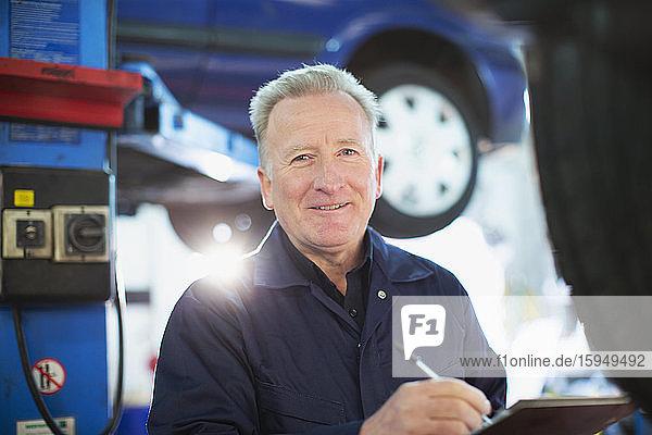 Porträt eines selbstbewussten männlichen Mechanikers mit Zwischenablage in einer Autowerkstatt