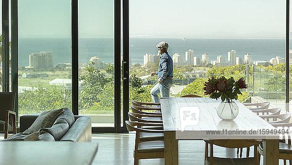 Mann steht auf sonniger Terrasse mit malerischem Blick auf den Ozean