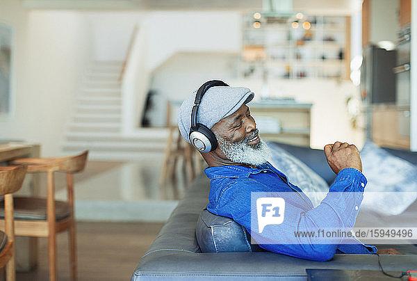 Glücklicher Mann mit Kopfhörern  der auf dem Wohnzimmersofa Musik hört