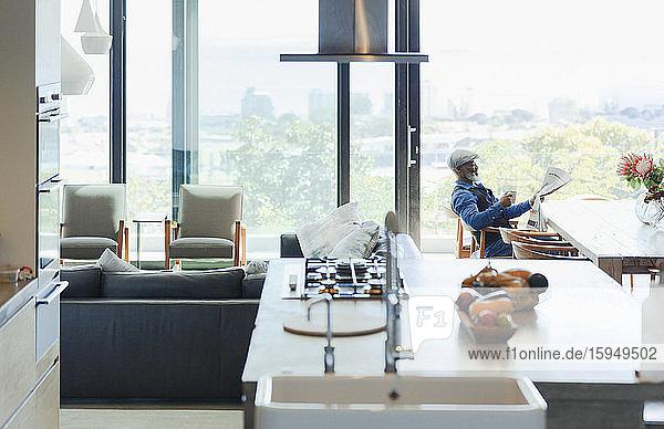 Mann liest Zeitung in modernem  offenem Haus