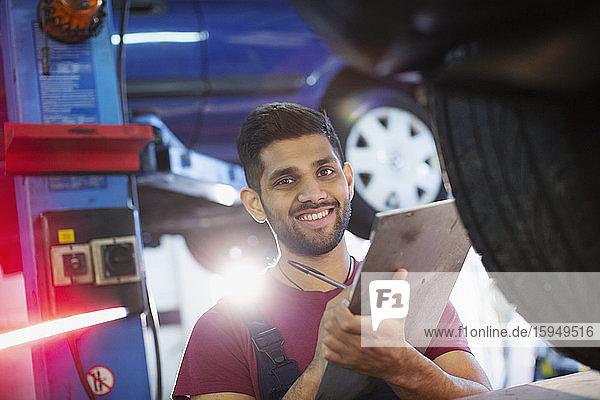 Porträt eines selbstbewussten  lächelnden männlichen Mechanikers mit Zwischenablage in einer Autowerkstatt