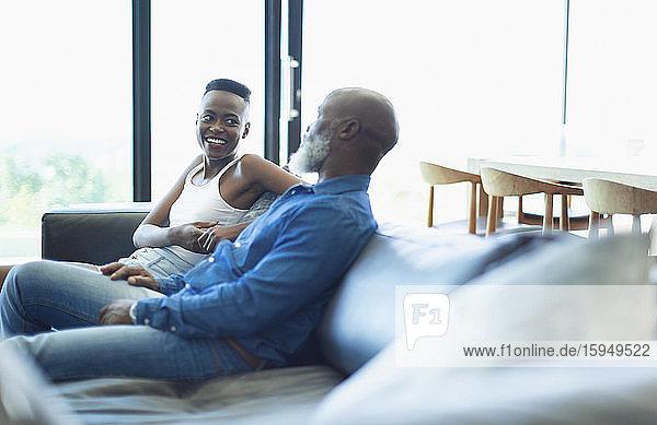 Vater und Tochter unterhalten sich auf dem Wohnzimmersofa