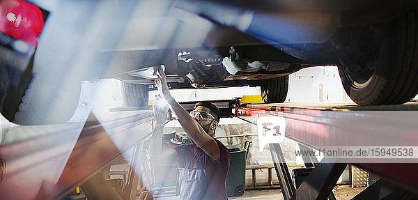 Männlicher Mechaniker  der unter dem Auto in einer Autowerkstatt arbeitet