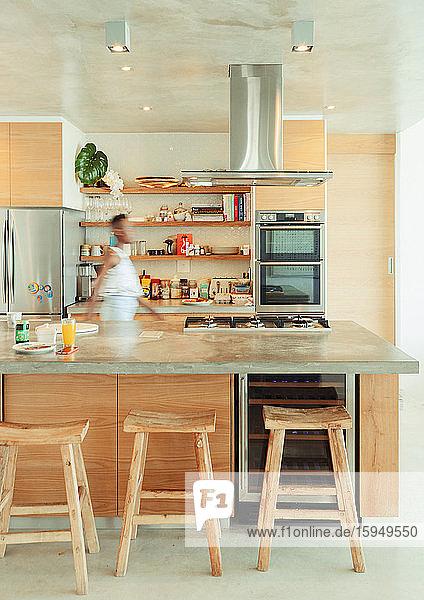 Frau geht in moderner Küche