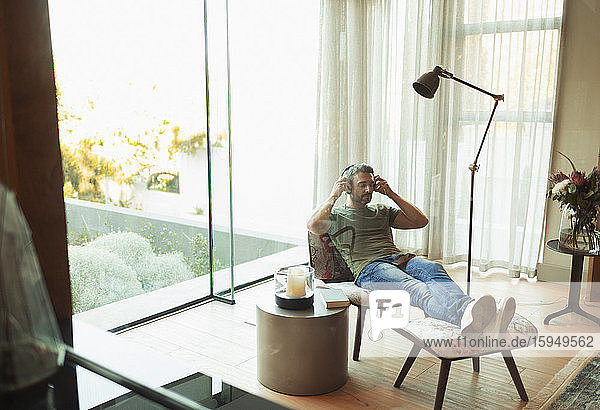 Mann entspannt sich  hört Musik mit Kopfhörern im Wohnzimmer