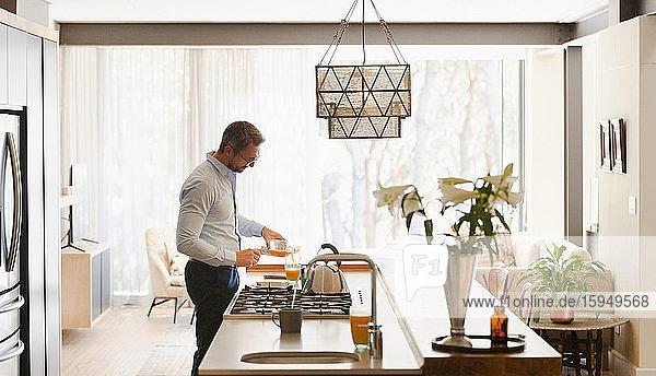 Geschäftsmann gießt Orangensaft in moderne Küche