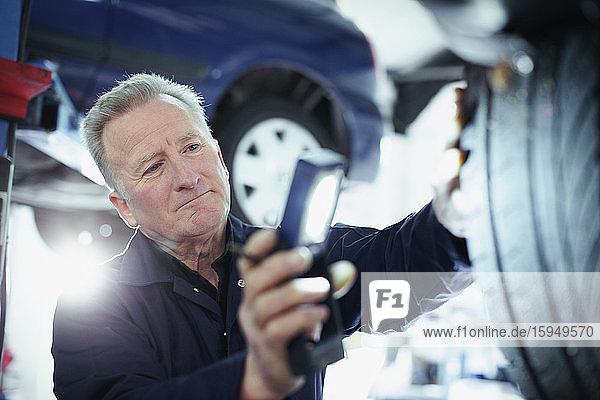 Männlicher Mechaniker mit Taschenlampe untersucht Reifen in Autowerkstatt