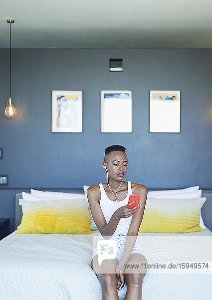 Junge Frau  die mit Kopfhörern und mp3-Player im Bett Musik hört
