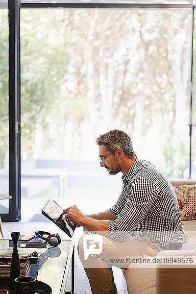 Geschäftsmann mit digitalem Tablet  der von zu Hause auf dem Sofa arbeitet