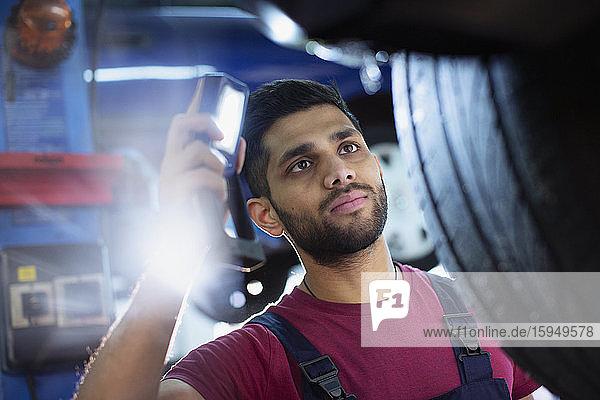 Fokussierter männlicher Mechaniker mit Taschenlampe untersucht Reifen in Autowerkstatt