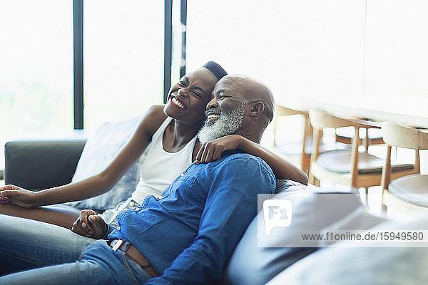 Glücklicher  liebevoller Vater und Tochter umarmen sich auf dem Wohnzimmersofa
