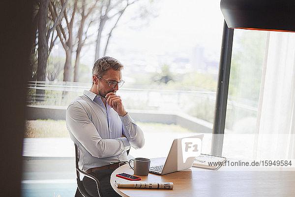 Geschäftsmann mit Laptop  der von zu Hause aus arbeitet