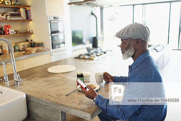 Mann genießt Frühstück und benutzt Smartphone in der Morgenküche