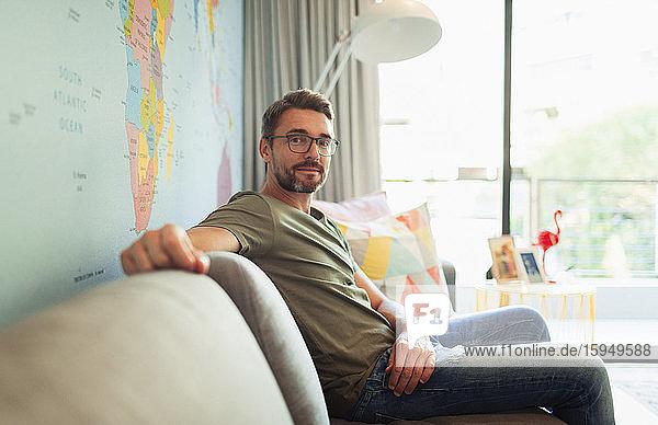 Porträt selbstbewusster Mann auf Wohnzimmer-Sofa sitzend