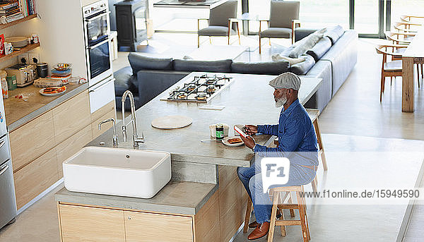 Mann frühstückt und benutzt Smartphone in moderner Küche