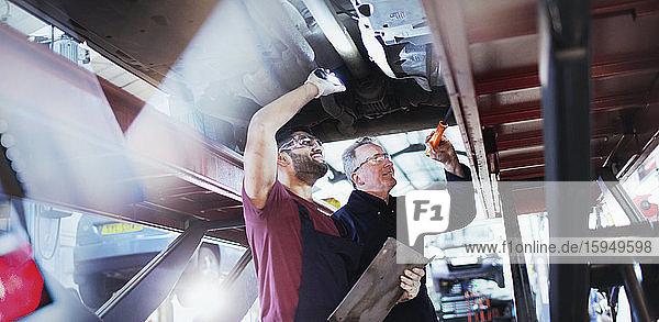 Männliche Mechaniker mit Taschenlampen  die in einer Autowerkstatt unter dem Auto arbeiten