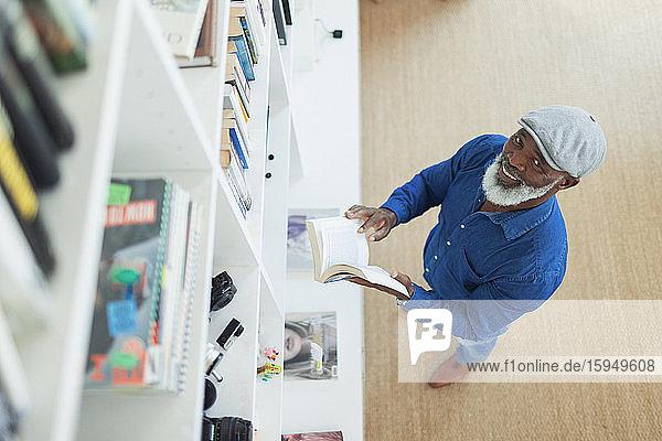 Porträt eines lächelnden Mannes beim Lesen eines Buches am Bücherregal