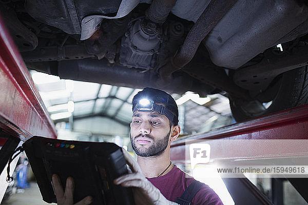 Männlicher Mechaniker mit Scheinwerfer und Diagnoseausrüstung arbeitet unter dem Auto in einer Autowerkstatt