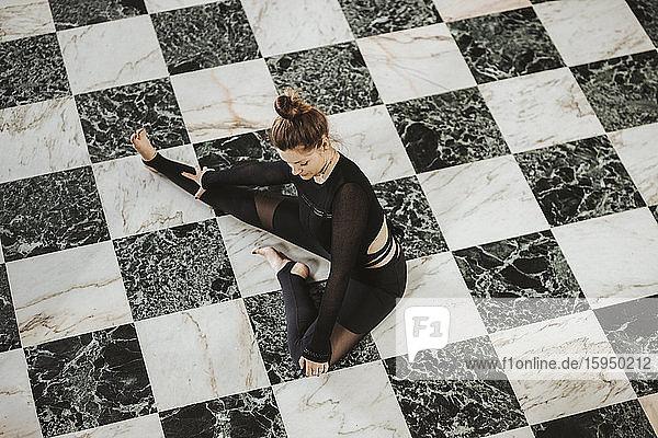 Frau praktiziert Yoga auf schwarz-weißem Boden zu Hause