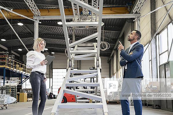 Geschäftsmann und junge Frau mit Tablette im Gespräch in einer Fabrik
