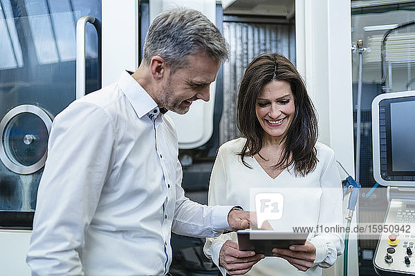 Geschäftsmann und Geschäftsfrau mit Tablette bei einem Arbeitstreffen in einer Fabrik