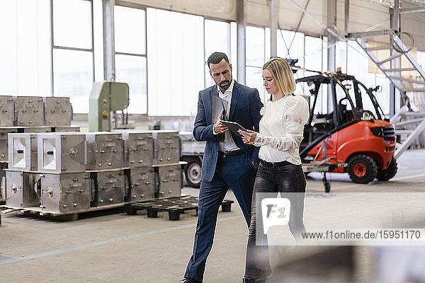 Geschäftsmann und junge Frau mit Tablette beim Gehen und Sprechen in einer Fabrik