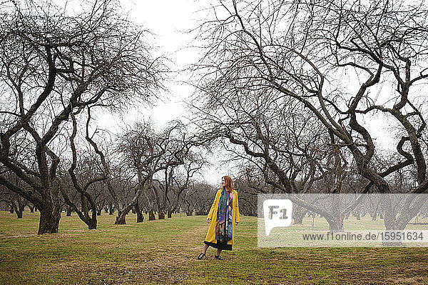 Full length of woman in yellow coat standing amidst bare trees at park  Russia  Moscow