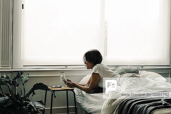 Frau  die morgens im Bett liegt und ihr Handy überprüft