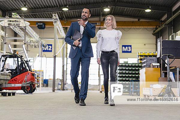 Geschäftsmann und junge Frau gehen und sprechen in einer Fabrik