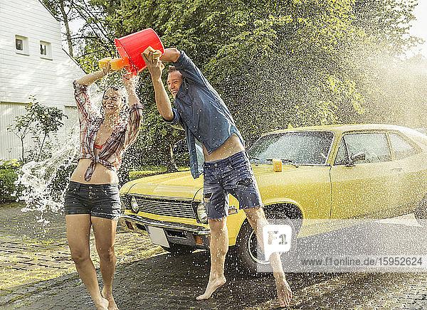 Freunde waschen im Sommer gelben Oldtimer und haben Spaß Freunde waschen im Sommer gelben Oldtimer und haben Spaß
