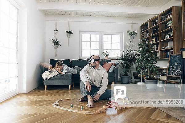 Vater sitzt inmitten von Spielzeug  benutzt eine VR-Brille  während der Sohn auf der Couch liegt