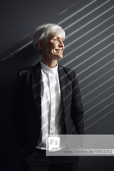 Porträt einer modischen älteren Geschäftsfrau vor grauer Wand  die in die Ferne schaut