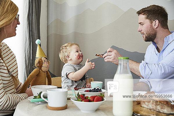 Verschmierter kleiner Junge mit seinen Eltern am Frühstückstisch