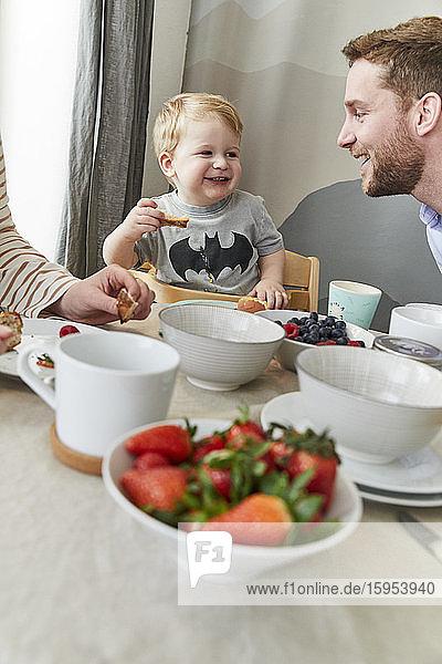 Porträt eines glücklichen kleinen Jungen  der sich mit seinem Vater am Frühstückstisch vergnügt