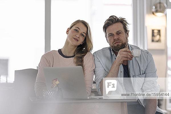 Porträt einer jungen Frau mit Laptop und eines Mannes in einem Cafe