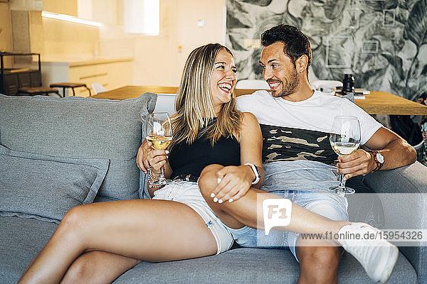 Glückliches Paar sitzt auf der Couch mit Weißweingläsern und amüsiert sich