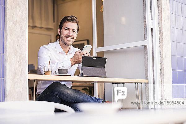 Junger Mann benutzt Tablet und Handy in einem Café