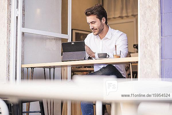 Junger Mann benutzt Tablette in einem Cafe